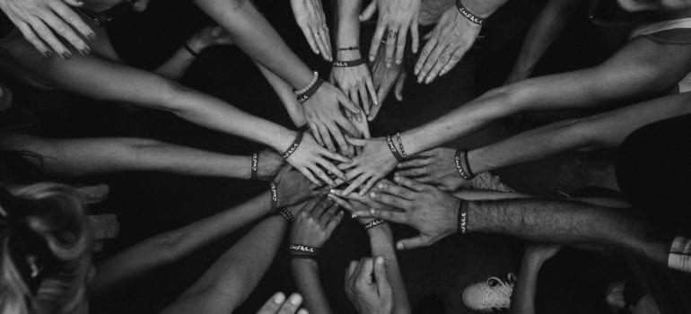 A collective of hand coming together like a pep talk