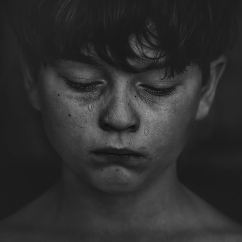 A young boy with tears rolling down his face