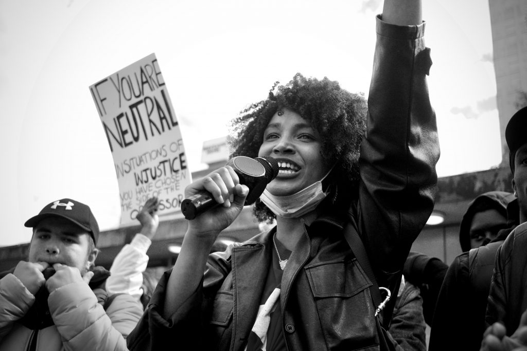 A photo of a woman speaking into a microphone at a protest